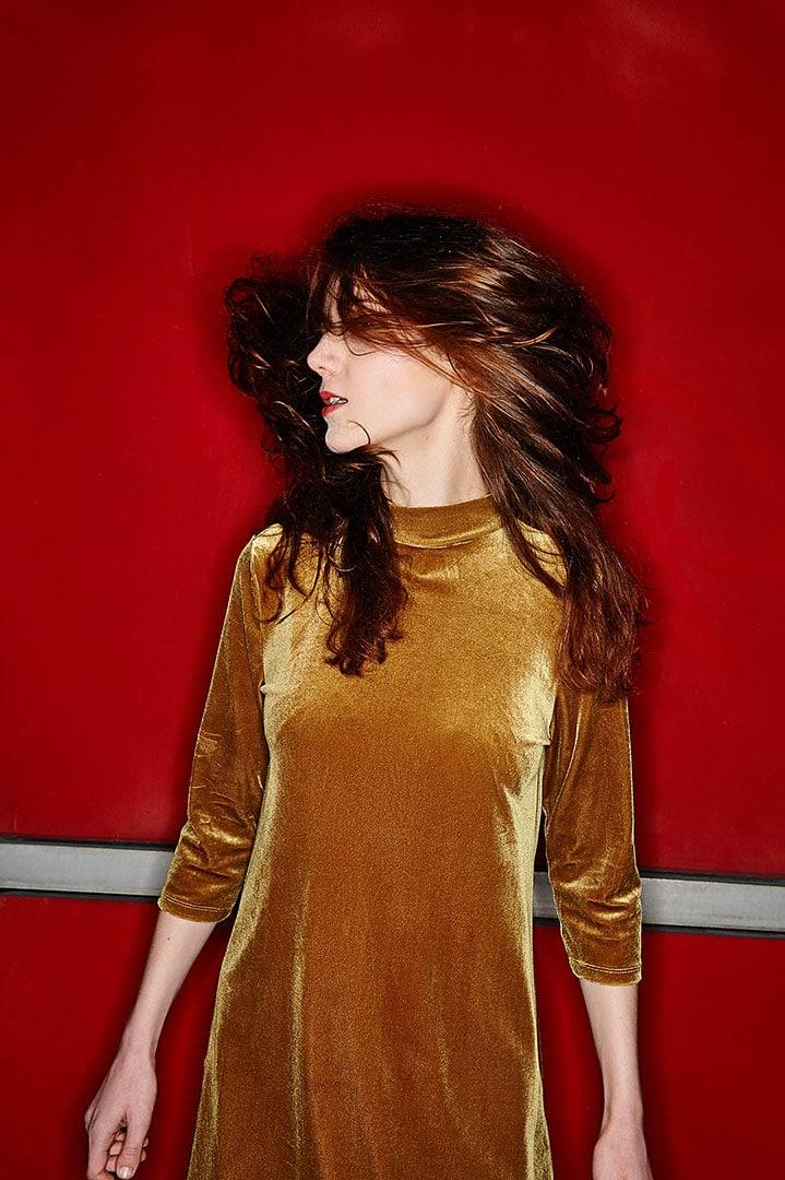 Frau mit wehenden Haaren vor roter Wand