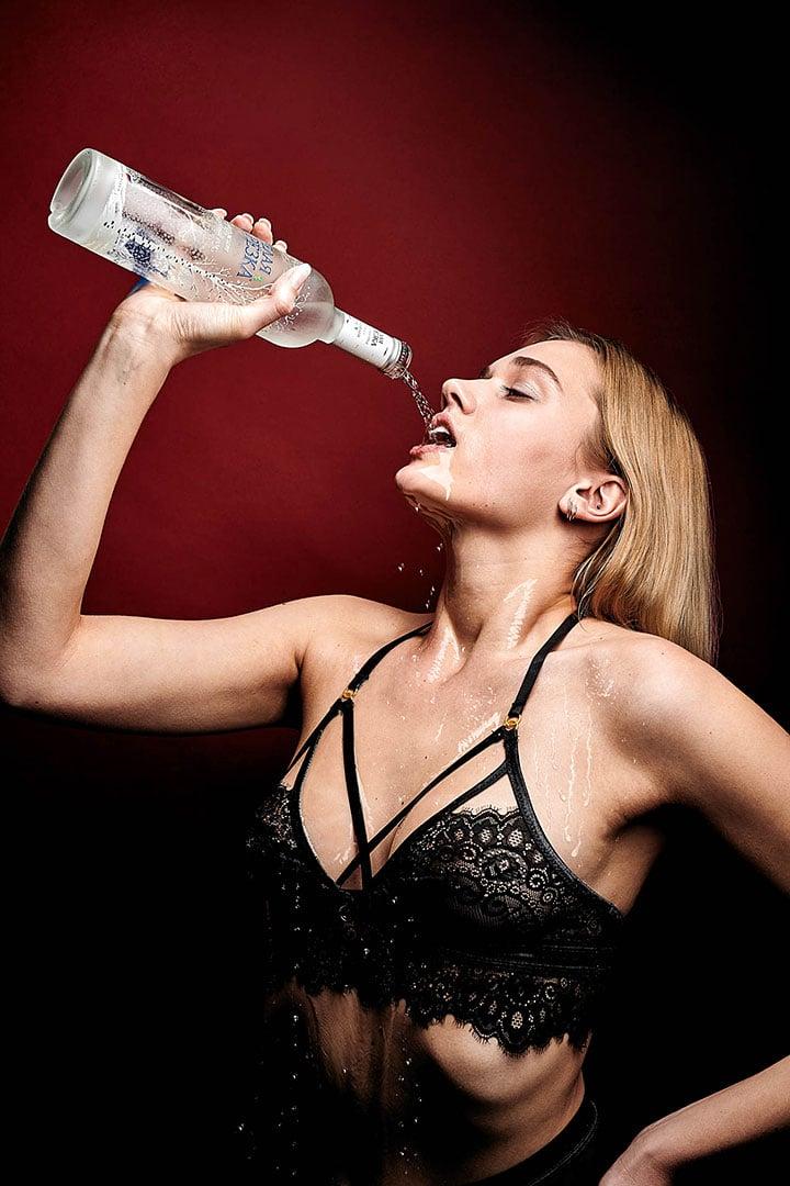 Sexy Model trinkt Vodka im Fotostudio