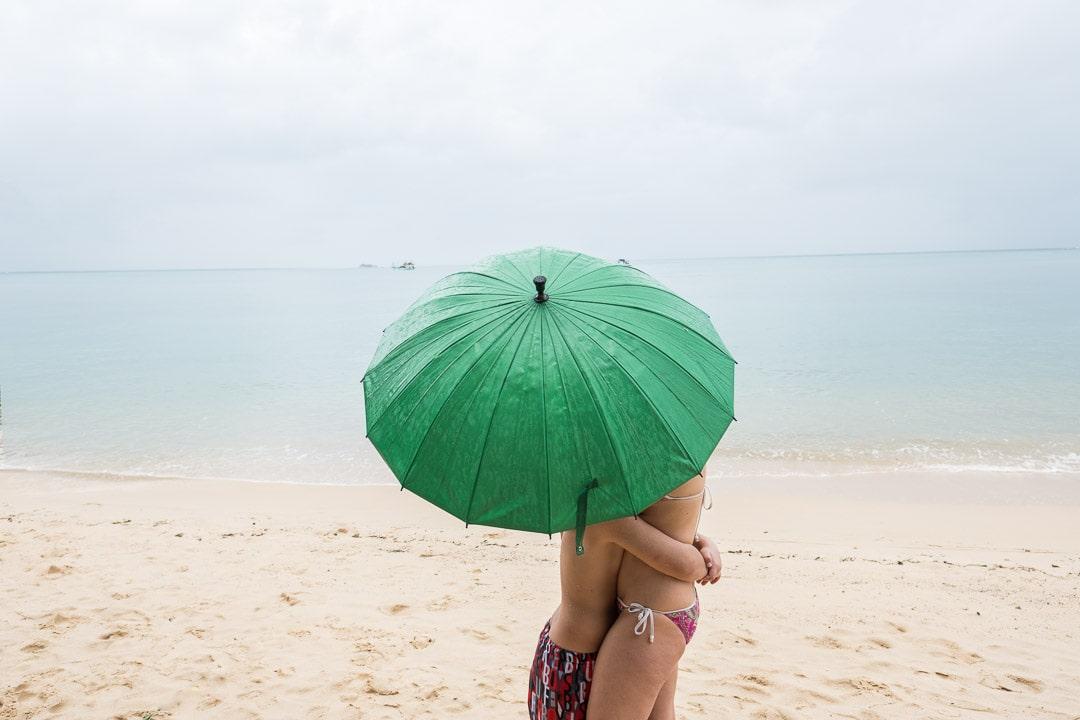 Das Photo zeigt zwei Menschen bei Regen am Strand