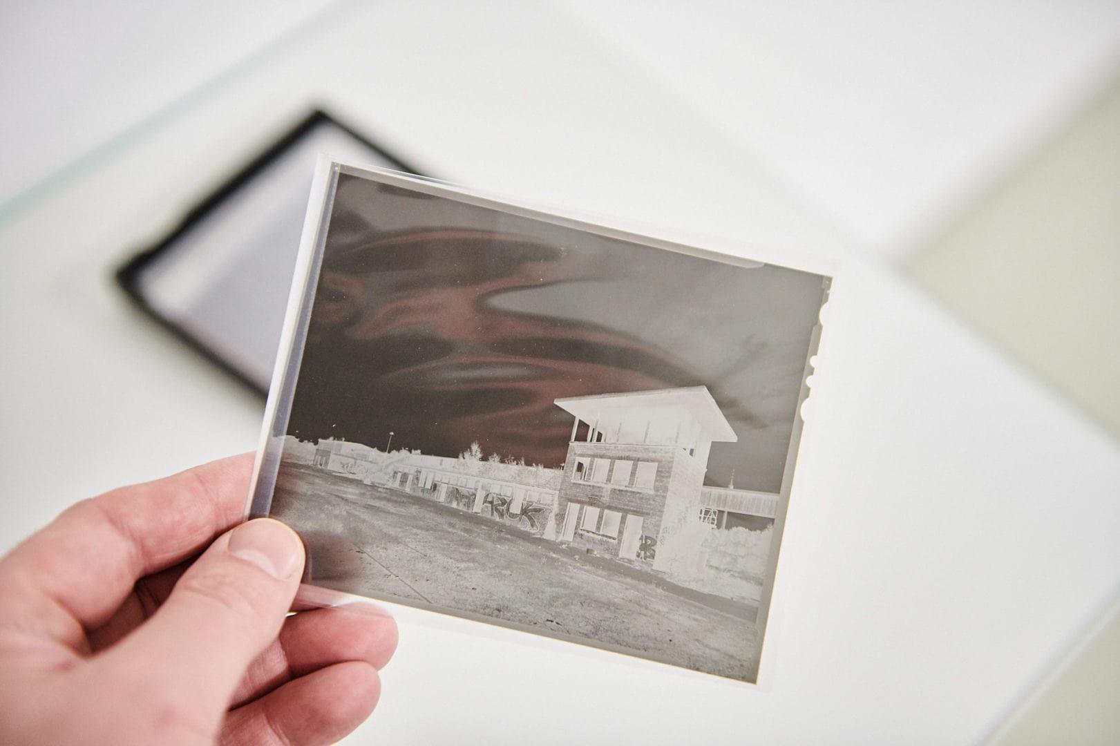 Fotograf hält Negativ eines Planfilms 4x5 in der Hand