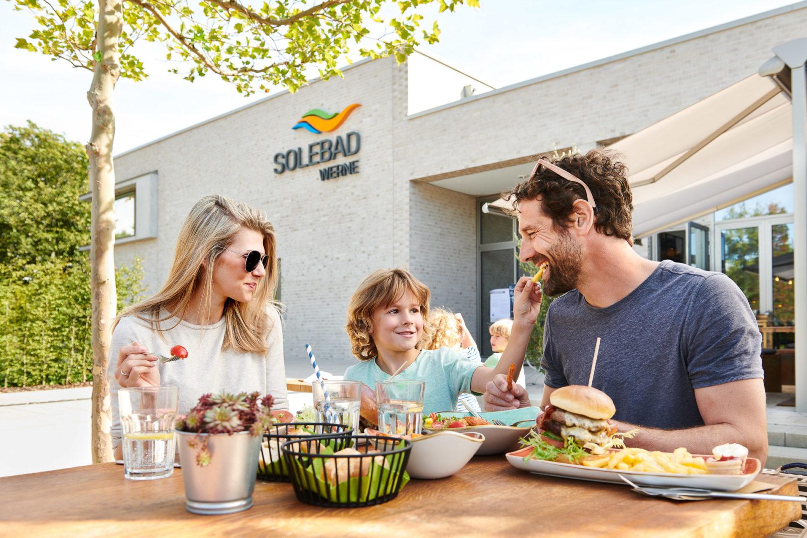 Fröhliche Familie speist vor dem Solebad Werne - Werbefotografie